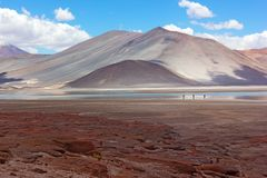 Majestically emotional landscape of Atacama Desert, Chile. Volcanic mountains and red rock formations separated by light blue lagoon royalty free stock images