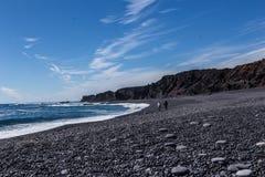 Volcanic pebble beach with black lava rocks Stock Photos