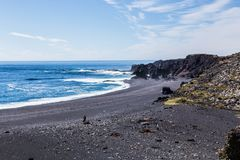 Volcanic pebble beach with black lava rocks Royalty Free Stock Images
