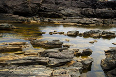 Volcanic rock. Clean water between yellow volcanic rock Stock Photo