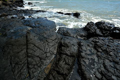 Volcanic rock in black. Volcanic rocks on beach beside sea, with black color and featured texture Stock Photography