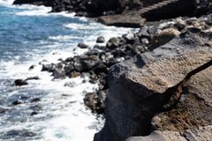 Volcanic rock close up with the rocky beach on the background, Tenerife, Canary islands, Spain - Image stock photography