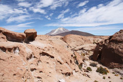 Volcanic rock and Ollague volcano in Atacama desert Royalty Free Stock Image