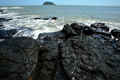 Volcanic rock by sea Royalty Free Stock Photos