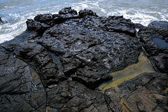 Volcanic rock beside sea Royalty Free Stock Images