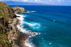 Volcanic rock, surf, and blue water on the Maui coaset Stock Image