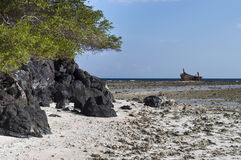 Volcanic Rock in shoreline. Volcanic rock in low tide shoreline with aground boat Royalty Free Stock Image