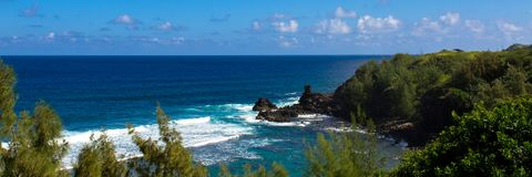 Volcanic rock, surf, and blue water on the Maui coaset Royalty Free Stock Photography