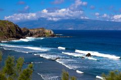 Volcanic rock, surf, and blue water on the Maui coaset Stock Photos