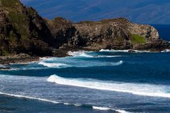 Volcanic rock, surf, and blue water on the Maui coaset Royalty Free Stock Image