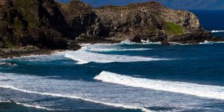 Volcanic rock, surf, and blue water on the Maui coaset Stock Images