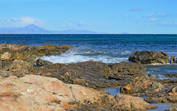 Volcanic Rock At The Waters Edge With A Distant Volcano Stock Photography