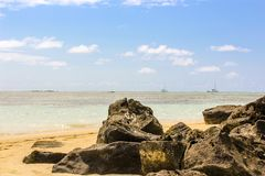 Mauritius Beach, Volcanic Rocks on the beach in the Indian Ocean, Mauritius, golden sand and boats royalty free stock images