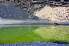 Volcanic rocks reflected in a green lake Stock Photo