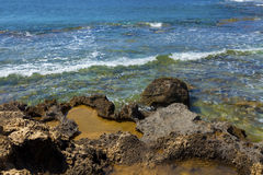 Volcanic rocks on the water edge. Volcanic rocks on the edge of clear sea water Stock Image