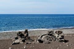 Volcanic rocky formation on black sand beach. Volcanic formation on a beach. Praia Formosa beach in Funchal on Madeira island, Portugal stock photos