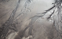 Volcanic sand shapes on the Canary island Tenerife beach, after ebb tide low tide. Black sand and white sand sculptures, made by the nature. Volcanic sand Stock Photos