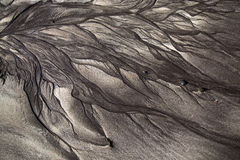 Volcanic sand shapes on the Canary island Tenerife beach, after ebb tide low tide. Black sand and white sand sculptures, made by the nature. Volcanic sand Royalty Free Stock Photography
