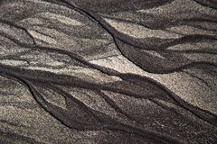 Volcanic sand shapes on the Canary island Tenerife beach, after ebb tide low tide. Black sand and white sand sculptures, made by the nature. Volcanic sand Royalty Free Stock Photos