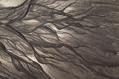 Volcanic sand shapes on the Canary island Tenerife beach, after ebb tide low tide. Stock Photos