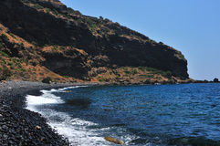 Volcanic seashore. Seashore with a mountain and volcanic rocks Royalty Free Stock Photography