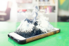 Volcanic Smartphon. Erupting volcano coming out of the screen of a smartphone