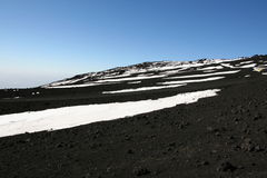 Volcanic soil, snow and sky on the top of Etna Stock Photo