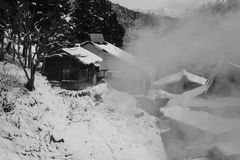 Volcanic spring shooting a plume of hot steam in snow covered hillside. With old mountain huts in Joshinetsu-Kogen National Park, Nagano, Japan Royalty Free Stock Photos