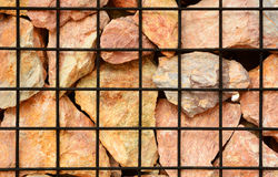 A volcanic stone and steel net fence texture Royalty Free Stock Photo