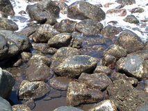 The volcanic stones on the beach. The waterworn black volcanic stones and sea water on the beach on the Ternate island, Indonesia royalty free stock photo