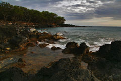 Volcanic stones of Hawaii in the sea Royalty Free Stock Photo
