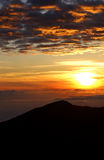 Volcanic Sunrise. The sun rises over the summit of Maui's 10,000ft Volcano Haleakala Royalty Free Stock Photo