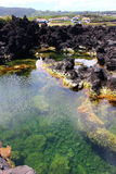 Volcanic Tidal Pool. A tidal pool amid rough igneous rocks on the coast of Terceira, one of the islands of Portugal's Azores Stock Photo