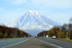 Volcano. Car goes on road on background of the snow-clad mountains Royalty Free Stock Photo