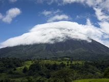Volcano Arenal, summit in front of blue sky with white clouds, green pastures and jungle stock photography
