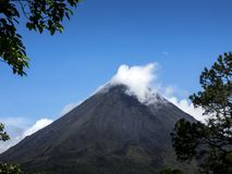 Volcano Arenal, summit in front of blue sky with white clouds stock image
