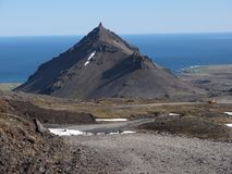 Volcano and Artic sea in Iceland. Scenic volcano with the Artic sea in the back ground blue sky blue sea beautiful water stock images