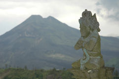 Volcano in Bali. Volcano with Hindu god statue in the foreground, Bali, Indonesia Stock Image