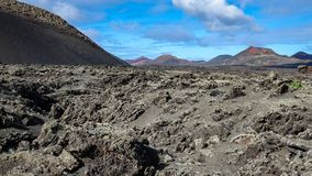 Volcano caldera crater with lava fields in the foreground. Lanzarote, Canary Islands royalty free stock photos