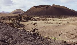Volcano caldera crater with lava fields in the foreground. Lanzarote, Canary Islands stock images