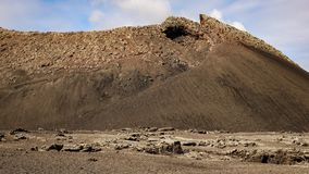 Volcano caldera crater with lava fields in the foreground. Lanzarote, Canary Islands royalty free stock image
