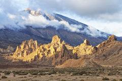 Volcano in clouds, dramatic rock formations in lunar scenery Stock Photo