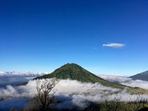 Volcano in the clouds royalty free stock photography