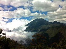 Volcano in clouds. A tropical view of a volcano at Lake Atitlan in Guatemala covered in brightly lit clouds Royalty Free Stock Images