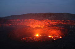 Volcano at dawn. Viewfrom the south crater rim into the active Erta Ale south crater with its lava lake. This picture shows the seldom situation of an overflow Stock Photo