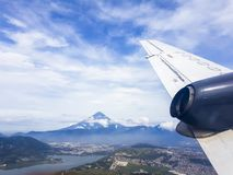 Volcano de Agua seen from a plane. A photo from Volcano de Agua, shot from a plane. The wing of the plane is visible. In front of the volcano you see the city royalty free stock image