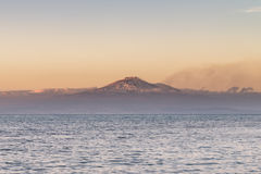 Volcano Etna seen from the sea. Seascape from Brucoli, a small seaside town in the province of Syracuse (Sicily), with volcano Etna in the background at sunset Royalty Free Stock Photography