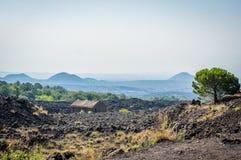 Volcano Etna sikt med gamla hus- och lavastenar omkring Arkivfoto
