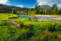 Volcano of Hornopiren. And green meadow with river. Chile royalty free stock photo