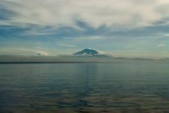 Volcano Mount Batur dal lato della laguna: nella priorità alta c'è una superficie dell'acqua con le riflessioni, nella distanza a Fotografia Stock Libera da Diritti